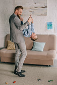 businessman in suit having fun together with little son at home, work and life balance concept