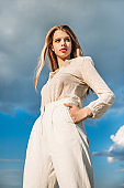 bottom view of elegant fashionable model posing in white stylish clothes with cloudy sky on background