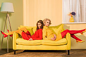 retro styled beautiful girls in colorful dresses lying on sofa back to back at home