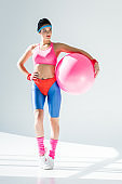 athletic young woman holding fitness ball and looking away on grey