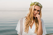 attractive bride in white dress and wreath of flowers touching lips and looking at camera on beach