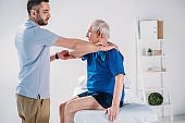side view of rehabilitation therapist doing massage to senior man on massage table