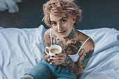 young tattooed girl with pink hair drinking coffee in bed at morning