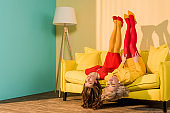 retro styled attractive girls in colorful dresses lying upside down on sofa at home