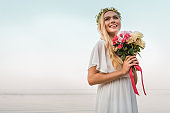smiling attractive bride in white dress and wreath holding wedding bouquet on beach