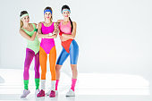 beautiful sporty young women in 80s style sportswear smiling at camera on grey