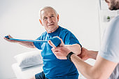 cropped shot of rehabilitation therapist assisting senior man exercising with rubber tape