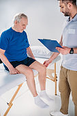 rehabilitation therapist with notepad checking senior mans knee on massage table on grey backdrop