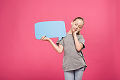 tired youngster relaxing and holding blue speech bubble, isolated on pink