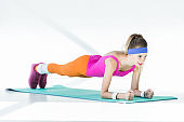 smiling young sportswoman doing plank on mat and looking away on grey