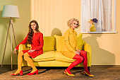 retro styled beautiful girls in colorful dresses sitting on sofa and looking at camera at home