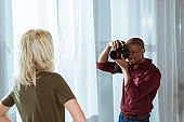 partial view of african american photographer taking photo of model in studio
