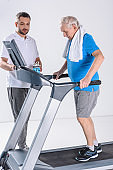 rehabilitation therapist assisting senior man with towel exercising on treadmill isolated on grey