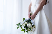 cropped view of bride in traditional dress holding wedding bouquet