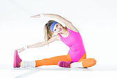 beautiful athletic girl stretching and smiling at camera on grey
