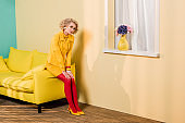 pensive woman in retro clothing sitting on yellow sofa at colorful apartment, doll house concept