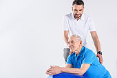 portrait of rehabilitation therapist making massage to senior man on fitness ball isolated on grey