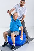 rehabilitation therapist assisting senior man exercising on fitness ball on grey backdrop