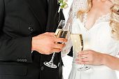 cropped shot of bride and groom clinking glasses of champagne isolated on white