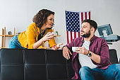 Couple holding cups of coffee and sitting on leather sofa
