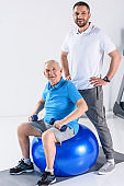 smiling rehabilitation therapist akimbo and senior man with dumbbells on fitness ball