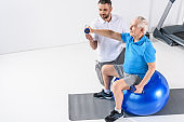 high angle view of rehabilitation therapist assisting senior man exercising with dumbbells on fitness ball