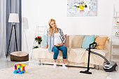 blonde pregnant woman sitting on sofa and looking at carpet with colorful blocks and vacuum cleaner