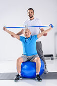 rehabilitation therapist assisting smiling senior man exercising with rubber tape on fitness ball