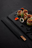 close-up view of delicious sushi roll with creamy eel and kimchi mayonnaise on slate board and chopsticks