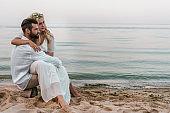 elegant groom and bride sitting on log on beach and looking away