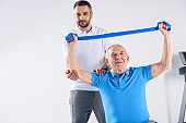portrait of rehabilitation therapist assisting senior man exercising with rubber tape on grey backdrop
