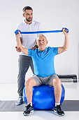 rehabilitation therapist assisting senior man exercising with rubber tape on fitness ball