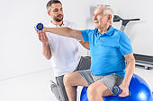 rehabilitation therapist assisting senior man exercising with dumbbells on fitness ball