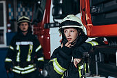 selective focus of female firefighter talking on portable radio set with colleague behind at fire department