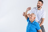 portrait of rehabilitation therapist helping senior man stretching isolated on grey