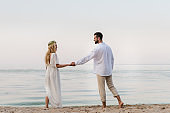 back view of bride and groom holding hands and looking at each other near ocean