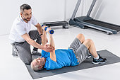 rehabilitation therapist assisting senior man exercising with dumbbells on mat