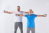 portrait of rehabilitation therapist and senior man exercising with rubber tapes isolated on grey