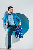 handsome stylish young man with shopping bag looking away while stepping through hole on grey