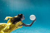 underwater picture of beautiful young woman in dress with balloon swimming in swimming pool