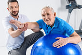 selective focus of rehabilitation therapist assisting senior man exercising on fitness ball