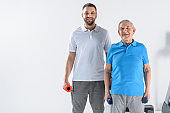 smiling rehabilitation therapist and senior man with dumbbells looking at camera on grey background