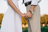 cropped shot of romantic young wedding couple holding hands