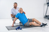 smiling rehabilitation therapist senior man with dumbbells on mat on grey backdrop