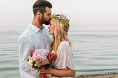 side view of handsome groom kissing bride forehead on beach