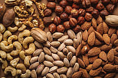 flat lay with tasty nuts arrangement on brown background