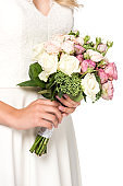 cropped shot of bride holding bouquet isolated on white