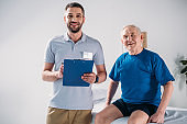 portrait of rehabilitation therapist with notepad and smiling senior man on massage table
