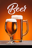 close up view of arrangement of glasses of beer  and beer lettering on orange backdrop
