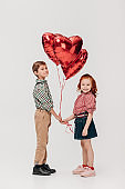 cute little kids holding heart shaped balloons and smiling at camera isolated on grey